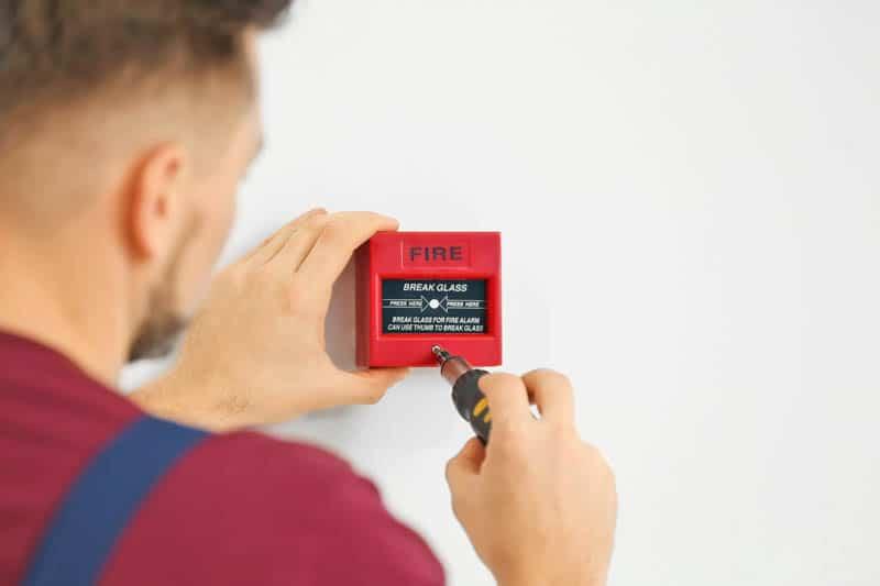 man fixing a fire alarm