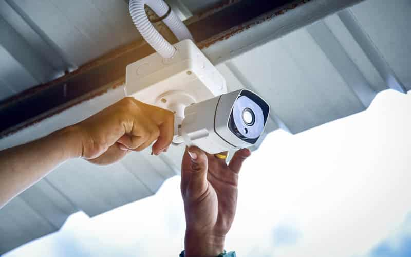 man installing security cctv camera on underside of roof
