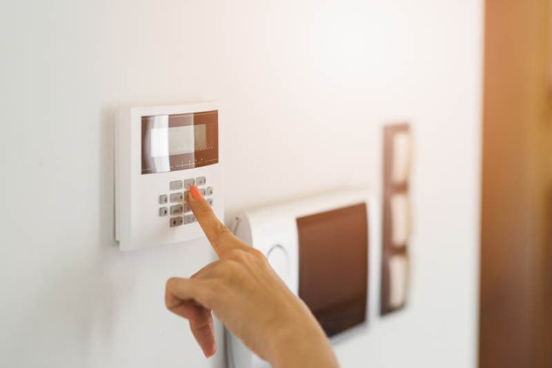 woman entering code on access keypad burgler alarm